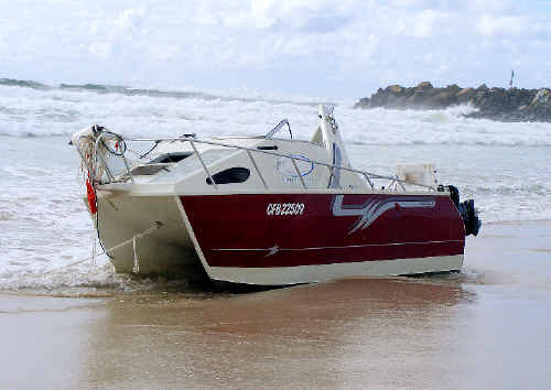 Rough seas crash on to Lighthouse Beach yesterday after this 6.5m charter fishing boat washed ashore after capsizing while attempting to cross the Richmond River bar at Ballina yesterday. All three people on board made it safely to shore.