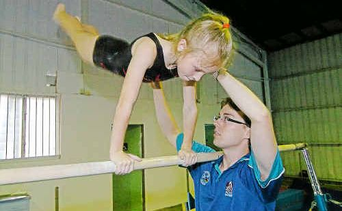 Dannalee Williams gets coaching on the uneven bars from Matt Woods at the new and bigger Gym club premises in Lester Street.
