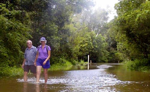 Grays Lane resident Isabel Reed and friend John Payne walk through floodwater to reach Mr Payne's car after the Tyagarah road was cut.