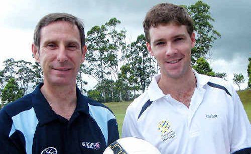 Rugby union referee Graham Cook (left) and young soccer referee Luke Mackney compare rule books.