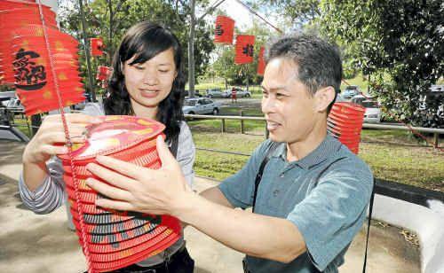 Nanning Daily journalist Li Jing and editor Wen Xue Jun put up a lantern.