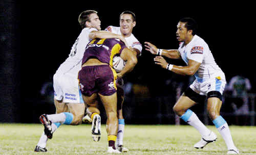 Gold Coast Titans defenders wrestle with Brisbane Bronco Ben Te'o in Friday night's trial match at the Briggs Road Sporting Complex.