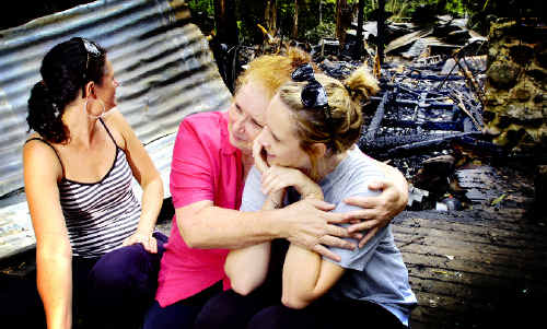 FAMILY SUPPORT: Sharon Kelly, of Billinudgel, hugs her grand-daughter Jessica Kelly (right) while daughter Mishka Kelly looks back at the devastating result of the fire that destroyed her mother's house. JAY CRONAN
