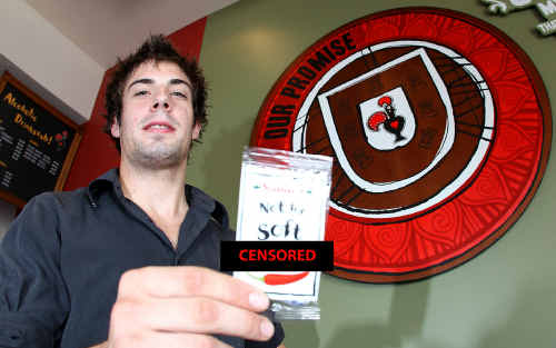Nando's Steven Davison holds one of the promotional condoms handed out with food at his popular Rockhampton store.