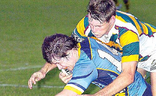 Sunshine Coast's David Wellington is stopped by the Darling Downs defence at Hervey Bay on Saturday night.