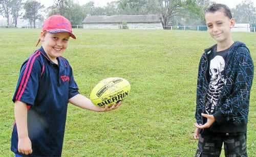 Ten-year-old Tyson Fett practises his AFL skills with nine-year-old Jayden Stewart at the AFL Redbacks Juniors and Auskick sign-on day.