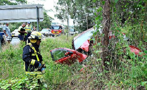 CRASH SCENE: The Ford Falcon wrapped around the tree and (left) Const. Wearne deals with the other problem.