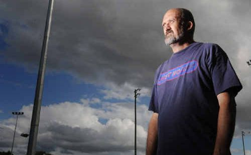 Treasurer of Grafton Hockey Association Rod Gould in front of the light towers at the hockey complex.