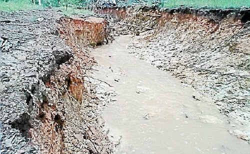 The bank of Rothman Road has been washed away after recent rain.