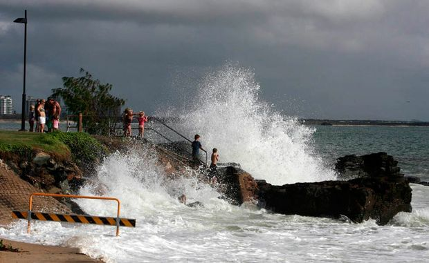 Children watched big surf at high tide on the rocks on Mooloolaba Esplanade.
