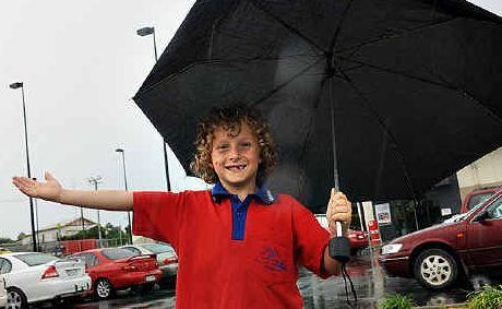 Gympie boy Sam Charlton braves the rain yesterday.