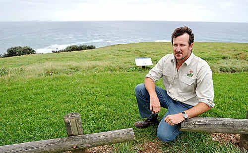 Justin Couper examines grassland on Woolgoolga Headland.