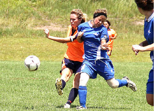 North Coast Football's Jasmin Courtenay gets crunched as she gets her shot away in an under 16s trial match against Far North Coast Football.