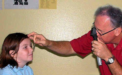Behavioural optometrist Richard Watt screens the eyes of Pialba State School student Haylee Philippi.