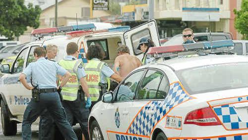 Police detain a man in Woongarra Street near Cornett's IGA.