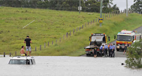 STRANDED: Despite countless warnings, two young men drove their vehicle into Deep Creek flood waters on East Deep Creek Road yesterday, becoming stranded in the middle of the crossing.