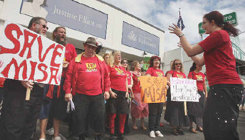 The Hearing Voices Choir, in red shirts, at the demonstration outside Federal MP Justine Elliot's Tweed Heads office to support a mental illness, drug and alcohol abuse program.