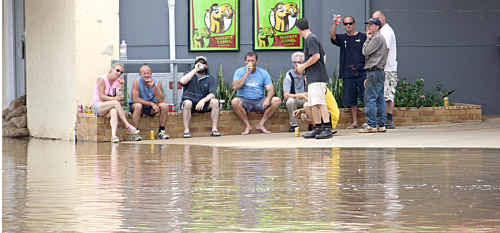 Patrons at the Corones Hotel in Wills Street, Charleville, enjoy a beer yesterday as they wait for the second wave of floodwater to arrive.
