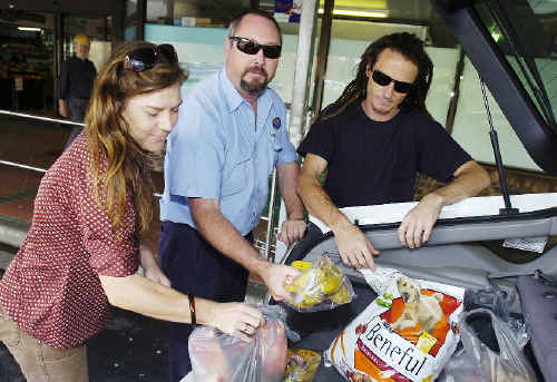 Rachel Smith, from North Lismore, gets a helping hand with groceries from taxi driver Anton Van Leuven and friend David Wilson.