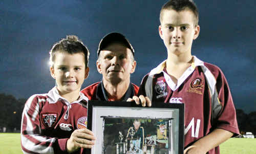Killarney Cutters president John Towells presents Sinclair Byrne's sons, Cody and Morgan, with a picture Mr Towells took of Mr Byrne in 2002, when he was named the Cutters' player of the year.