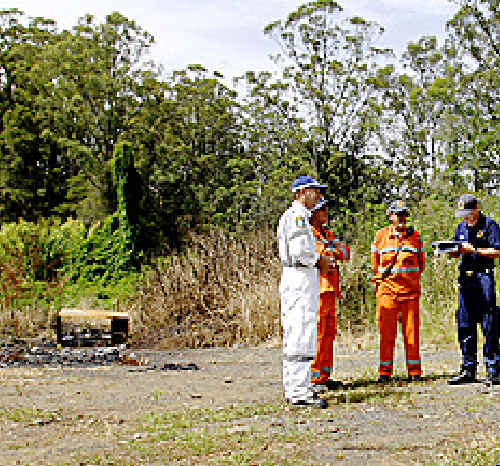 Police and SES workers at the scene of the burnt-out vehicle near Barkers Vale in December 2008.
