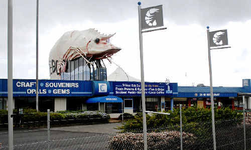 Last legs: Chainlink security fencing fails to deter vandals who have embellished Ballina's tired-looking tribute to the sea as it awaits timely dismantlement.
