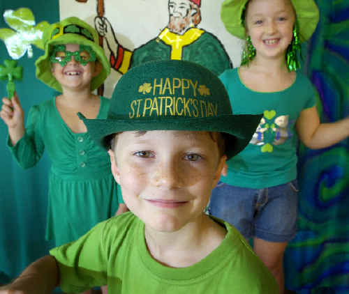 Our Lady of Lourdes Primary School students Gabby Venn of Year 2, 7 (left), Paddy Molloy Kindergarten, 5 and Alyssa Livotto Year 2, 7, get set for St Patrick's Day celebrations.