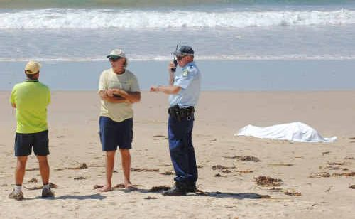 Brooms Head caravan park manager Darren Mussared and Broom Head RFS co-ordinator and resident Boots Towner speak with Sergeant Darren Williams on Brooms Head beach.