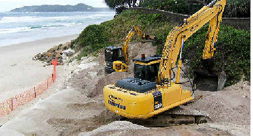 Heavy earthmoving equipment reinforces the shoreline at Belongil after a court order was given that allowed residents to protect their homes against a predicted storm surge caused by Cyclone Ului.