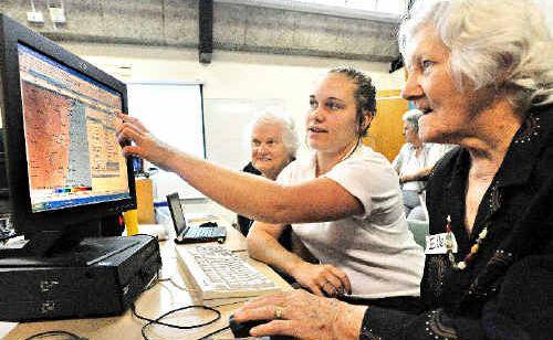 Ellen Dodd and Beth Rogers navigate the Bureau of Meteorology website with the help of Fiona Mackay.