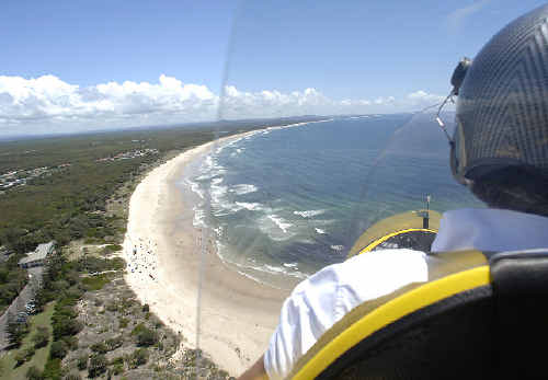 Flying instructor Peter Coulter, of East Coast Autogyro, flying over Evans Head on a shark watch patrol.