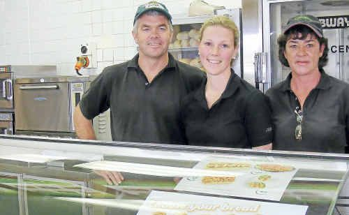 Warwick Subway owners Ron and Belinda Christie hand over the keys to new owner Bec Van Bennekom (middle) today.