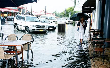 A woman walks through flood waters in Lawson Street.