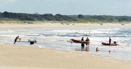 Evans Head surf lifesavers return to the beach after a search for a man missing in the surf at Main Beach, Evans Head, yesterday.