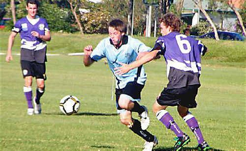 Action from the Ballina v Pottsville match. Ballina's Andrew Lundie (in blue) attacks while attempting to get away from Pottsville's Jarred Lee.