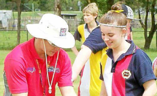 Jeff Newnham demonstrates a handball to Warwick High year nine student Demi Quirk during an AFL demonstration.