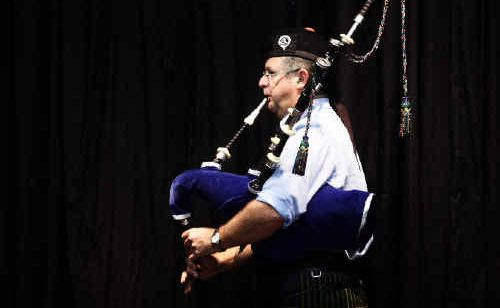 Alastair McInness stands under the stage light while performing in the open hornpipe competition.