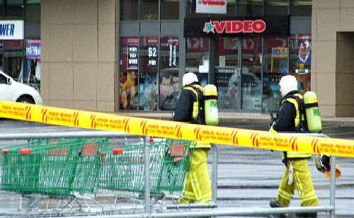 On the job: Firemen with breathing apparatus tackle the fire at Ballina Fair shopping centre yesterday.