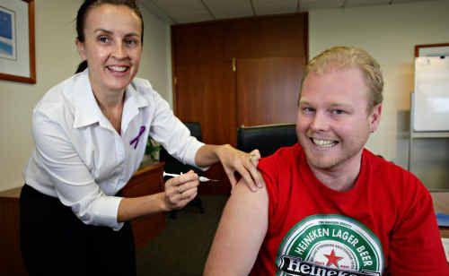 Taking the shot: Jane Johnston gives Joshua Baker a seasonal flu vaccination.