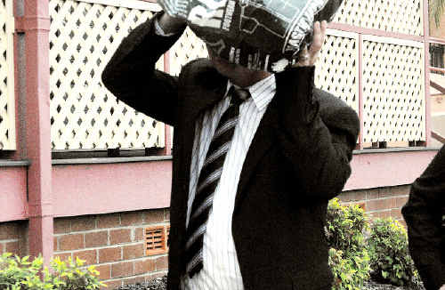Ashamed: Paul Sweeney hides his face behind a bag leaving Lismore Court House after pleading guilty to drug charges.
