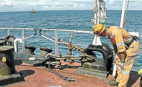 A salvage crew member inspects the chain holding the boom in place.