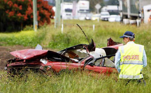 A policeman inspects part of the wreckage of a fatal accident on the Warrego Highway which involved a sedan and a semitrailer.