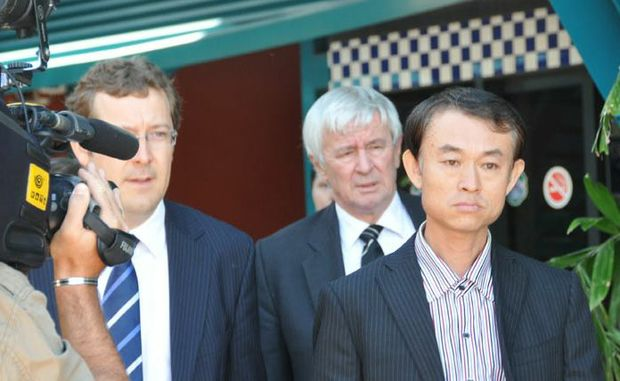 Shen Neng 1 master Wang Jichang (right) leaves Gladstone Police Station with barrister Tony Glynn and defence solicitor Matthew Hockaday (left)