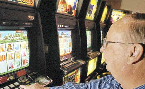 Sydney, May 3, 2004. A punter playing the poker machines in a Sydney club today. Clubs NSW released a report today claiming planned state government tax increases, including a proposed poker machine tax, will cost the industry up to 24,000 jobs and put up the price of beer.