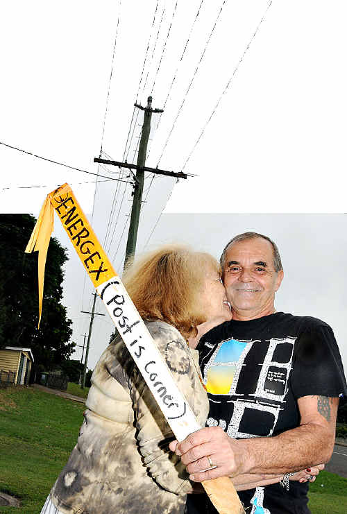 All over: Evelyn Despea kisses husband Leon after he took the Energex marker from the front of their Myall Street home. Energex scrapped the planned route for high voltage powerlines through Gympie after a public outcry.