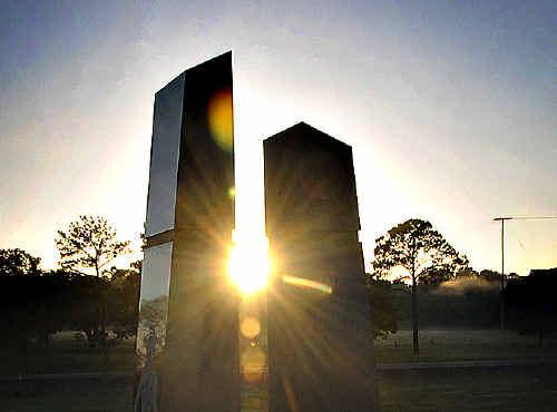 The sun rises between the pillars of the cenotaph.