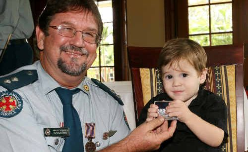 AMBO PRIDE: Emu Park's Ashley Wessels shows grandson William Wessels his long service medal.