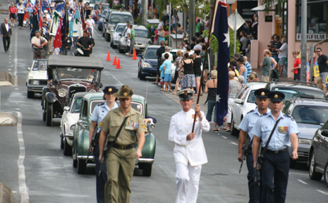 Corporal Tim Roseler, Corporal Sara Cannon (obscured) CPO Peter McKellin carrying flag, Corporal Bryan Hudson and Corporal Brad Withers lead the ANZAC Day march down the main street of Airlie Beach.