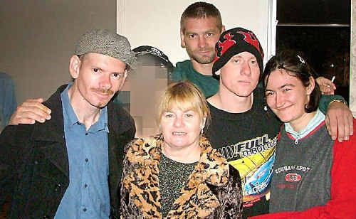 """A smiling killer (face obscured) with a """"family"""" photograph showing (from left) murder victim Michael Thompson, Margaret Thompson, John Thompson, Amanda Curtis and (at back) Nathan Thompson. Weeks after this photograph was taken in 2005, the killer, who had been befriended by the Thompson family, brutalised and murdered Michael."""