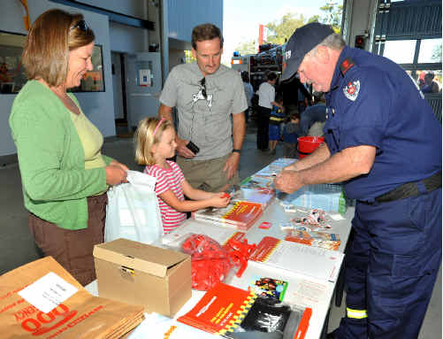 Sawtell fire captain Keith Rhoades packs a bag of goodies for Rebeccah and her parents Andrew and Janine (right). Far left: Firefighter Mick Gibbons demonstrates a fire hose to Sam Melinz of East Boambee.